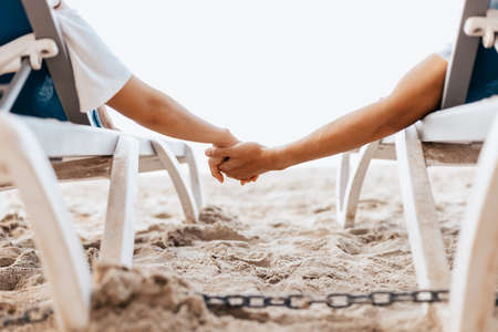 Couple of lovers sitting on beach chair holding hands on the beach in the morning.  Newlywed couple on a romantic vacation
