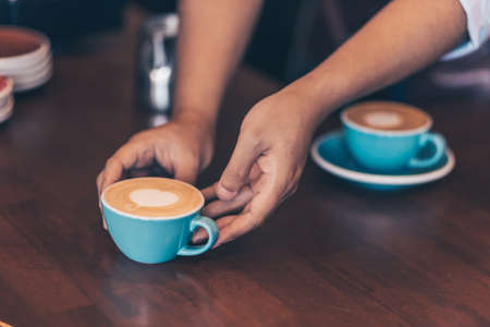 Barista serving a coffee to customer at the coffee shop.