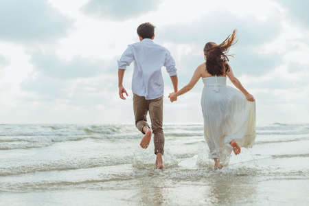 Love young couple holding hands and running on the beach. Holiday and vocation concept.