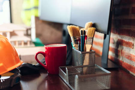 paint brush and pencil in pencil box, cup of coffee and sefty helmet on the table.