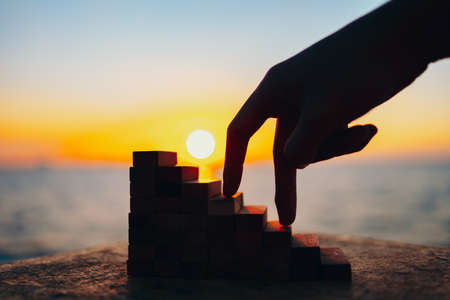 finger like a person stepping up wood block stacking as step stair and sun background. Business success, win concept.