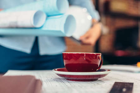Cup of coffee on drawing plan in the room and architecture hold plan design blur background. Banque d'images