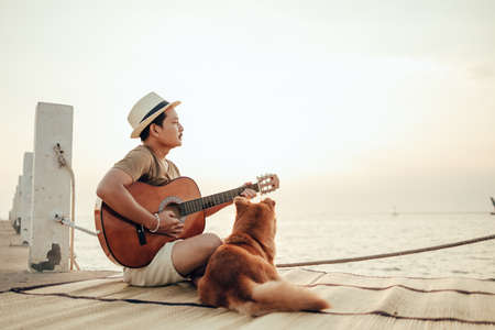 A man wear straw hat and playing guitar music song near the sea sunset with a dog pet.Travel, Vocation, Holiday concept.