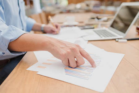 Businessman hands point paper graph and checking document data calculator for calculate budget accountancy. finance and accounting concept