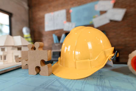 safety helmets  and jigsaw on design plan on the table at site construction. Banque d'images