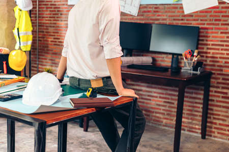 industry manager, engineer, businessman sitting on table and checking blueprint, drawing plan on the wall in the room in office.