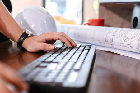 Architecture typing on keyboard for working and safty helmet, planing design on the table.