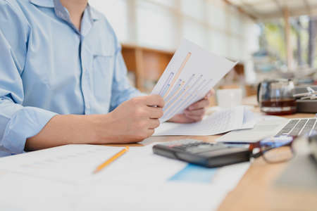 Businessman hold paper graph and checking document data calculator for calculate budget accountancy. finance and accounting concept