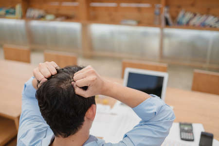 Tired businessman at workplace in office holding his headache or angry. Overworking, making mistake, stress, termination, fail, bad, sad tired or depression concept Banque d'images