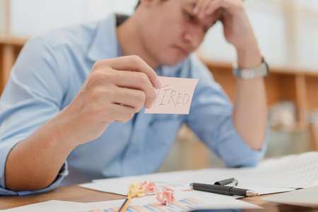 Businessman headache and hold sticky note with text