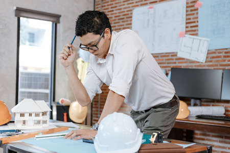 industry manager, engineer, businessman reading and checking blueprint, drawing plan in the room in office.