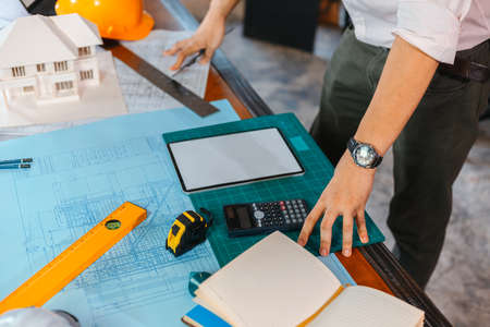 industry manager, engineer, businessman reading and checking blueprint, drawing  in the room