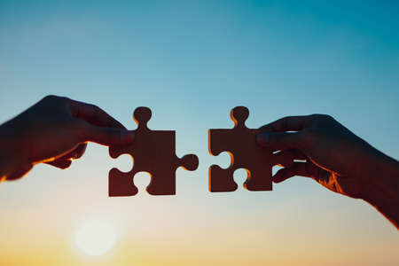two hands of businessman to join jigsaw puzzle piece with sky background. business partnership, teamwork, success and strategy Banque d'images