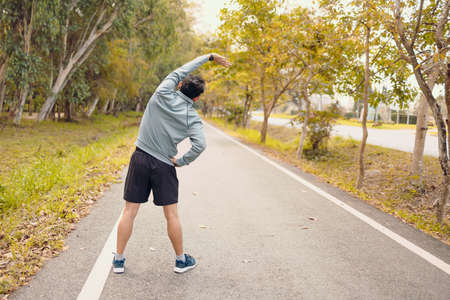 young man stretching in the park before running. Young man workout before fitness training at the park. Healthy and exercise young man warming up on the road beside the forest.