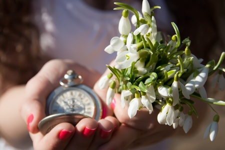 Snowdrops and old watch in the women hands