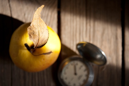 Apple and a pocket watch on a wooden surface