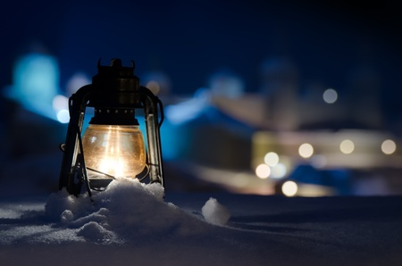 On the background of an ancient fortress old gas lamp is standing on the snow lighting up small area around.