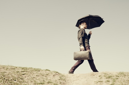 A man stepping up against a sky background with a suitcase and umbrella