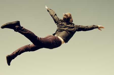 Young man flying in sky.