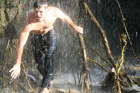 Guy under a waterfall in the forest. Stock Photo