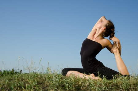 Yoga woman on green grass  Sky background