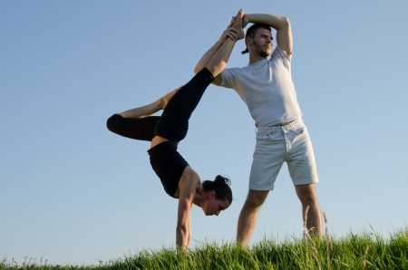 Man and woman doing acroyoga. Outdoor. Stock Photo