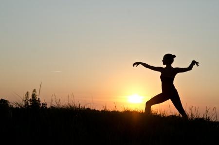 taichi: Woman praticing tai chi chuan at sunset.