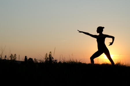 Woman praticing tai chi chuan at sunset. photo