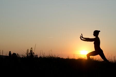 chi: Woman praticing tai chi chuan at sunset.