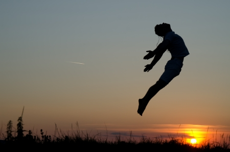 Guy jumping over sunset. Stock Photo
