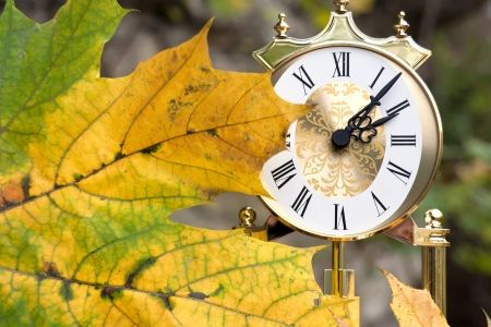 Concept Autumn. Clock and fallen leaf. Stock Photo