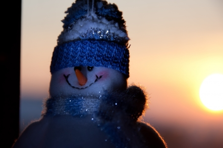 Snowman and a sunset in the background.