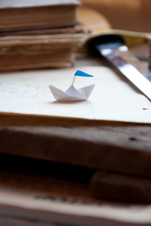 Treasure Island. Old map, paper boat, and dagger.