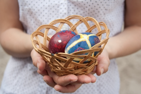 Woman hand holding basket with Easter eggs. Stock Photo