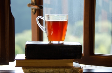 Cup of tea on a stack of books and  open window.