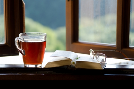 Сup of tea, chamomile flower and an open book on the window. The concept of reading.