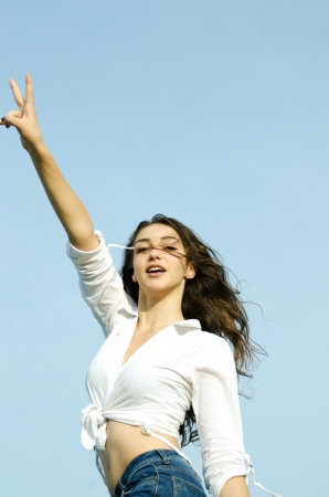 Pretty young woman showing gesture that everything is Victory, against blue sky  photo