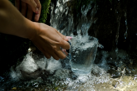 Glass of water by waterfall. Human hand holding glass pouring fresh drink water.