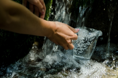 Glass of water by waterfall. Human hand holding glass pouring fresh drink water. Stock Photo - 21066436