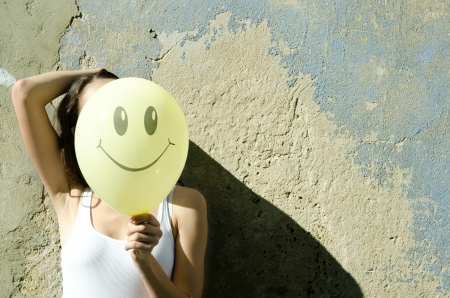 Yellow balloon with smile and  girl, wall background.