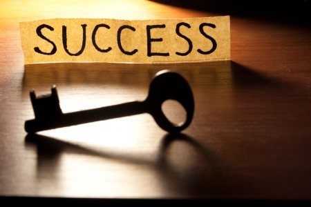 The Key to Success. Key on a wooden background. photo