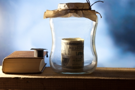 Jar with money, college graduation cap and book.  photo