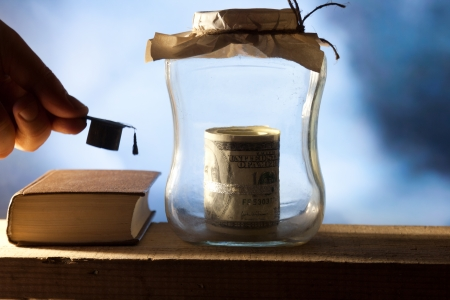 Jar with money, college graduation cap and book. Stock Photo - 22582534