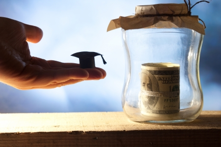 Jar with money, college graduation cap and book.  Stock Photo