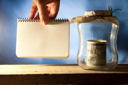 Saving money jar. Hand holding blank.