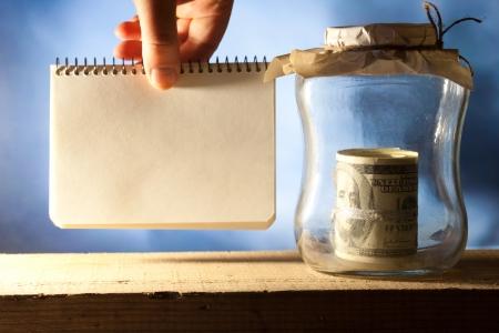 tax tips: Saving money jar. Hand holding blank.