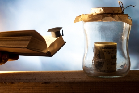 Jar with money, college graduation cap and open book. Stock Photo - 22582543
