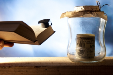 Jar with money, college graduation cap and open book. Stock Photo - 22582545