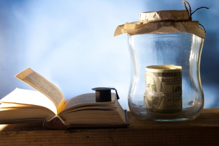 Jar with money, college graduation cap and open book.  photo