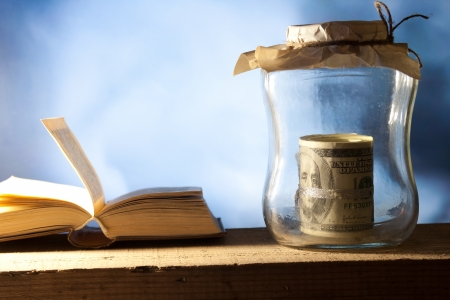 tax tips: Saving money jarand. Open book Stock Photo